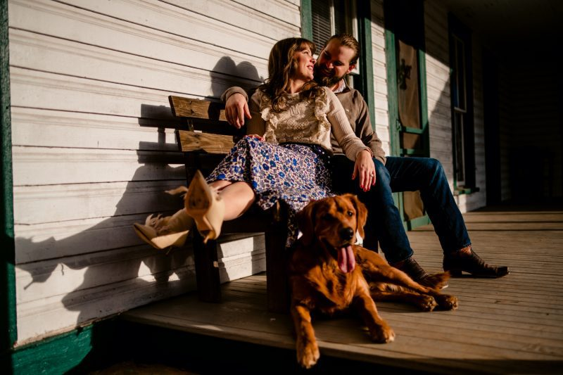 Engagement photoshoot of couple sitting on a bench with their dog