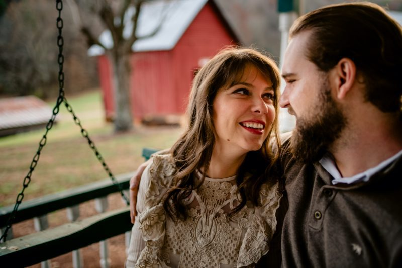 Couple sitting on a porch swing smiling at each other