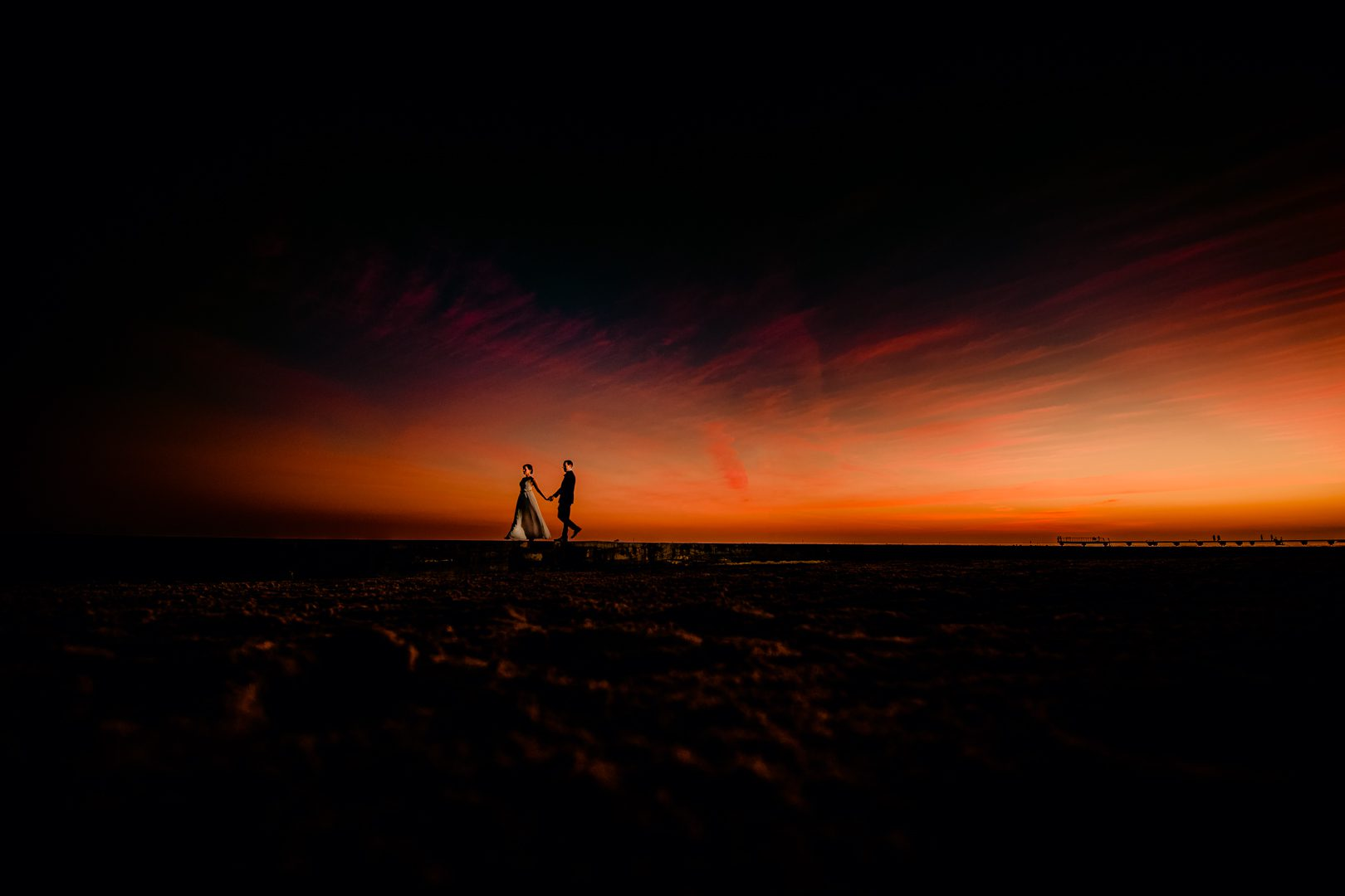 Couple Hold Hands During Sunset On Their Wedding Day
