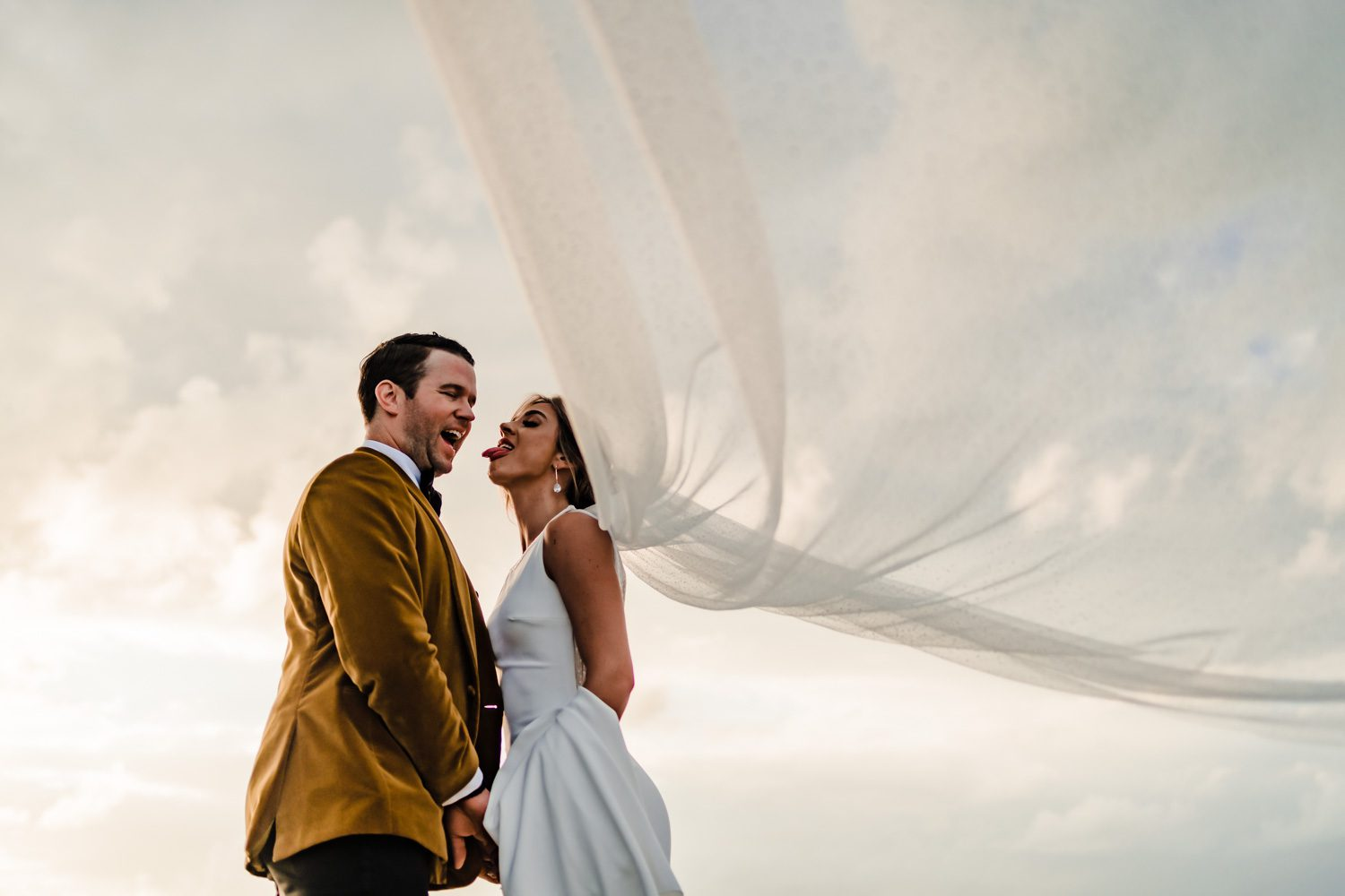 Couple With Brides Veil Flowing In Wind During Wedding Day