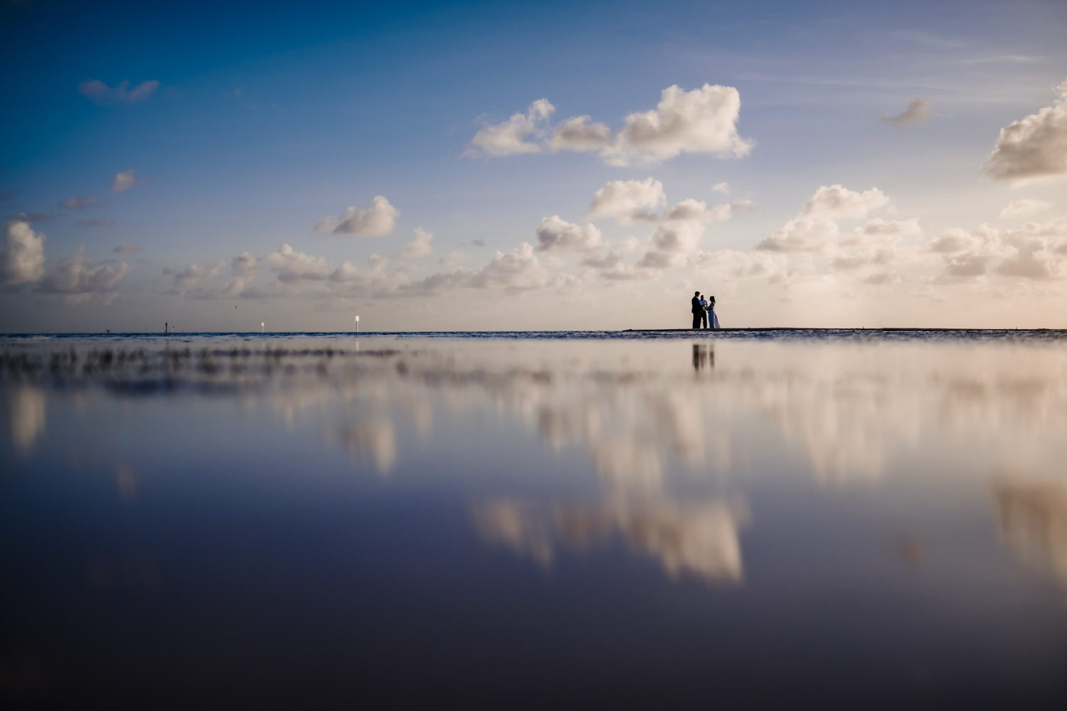 Couple Pose On The Beach With A Reflective Sky On Sand During Their Wedding Day