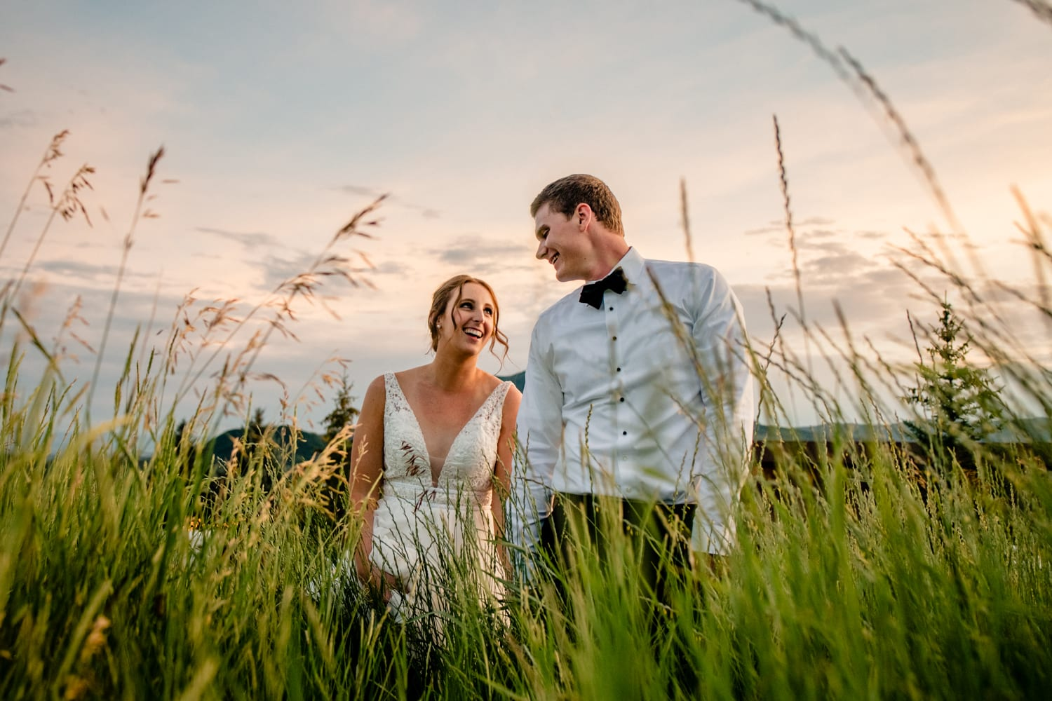 Couple Walk In Field During Sunset Wedding Photo Session