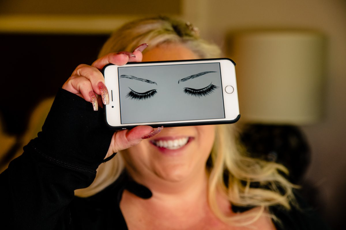 Bride Holds Up Phone Over Eyes Playfully Before Wedding Day