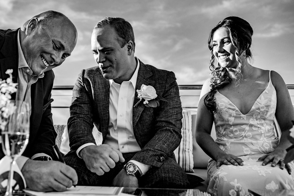 Bride, groom, and best man laugh together at Little Palm Island, Florida Keys.