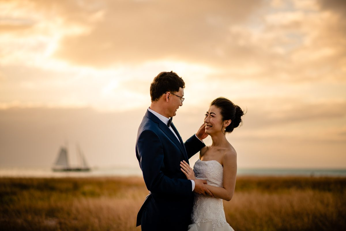 Newly Wed Couple Post During Sunset With A Sailboat In Background At Fort Zachary Taylor, Key West