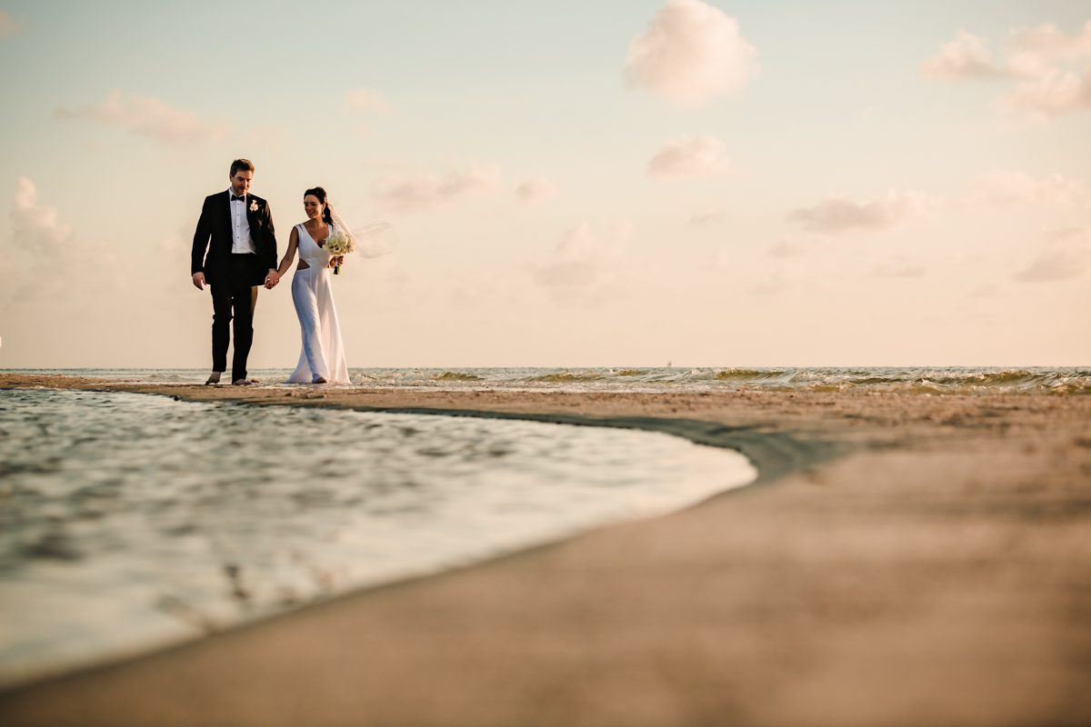 Newly wed couple walk on the sand at Little Palm Island in Florida Keys.