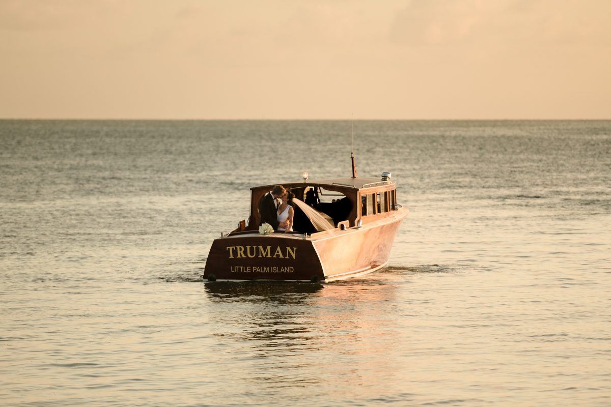 Wedding boat floats into sunset at Little Palm Island, Florida Keys.