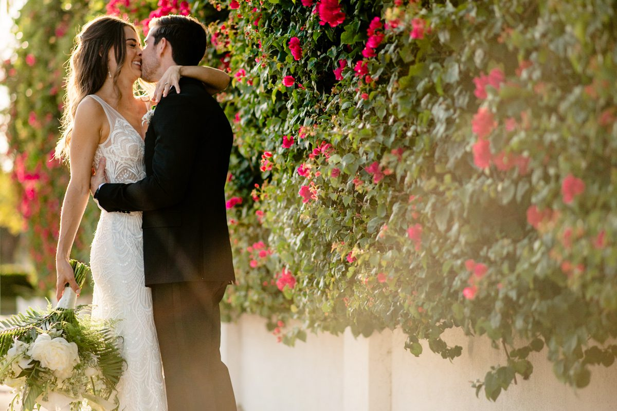 Couple kiss next to a wall of flowers in Key West, Florida.