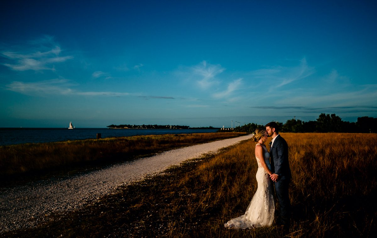Newly wedded couple hug amongst large field of grass with blue skies at Fort Zachary Taylor.