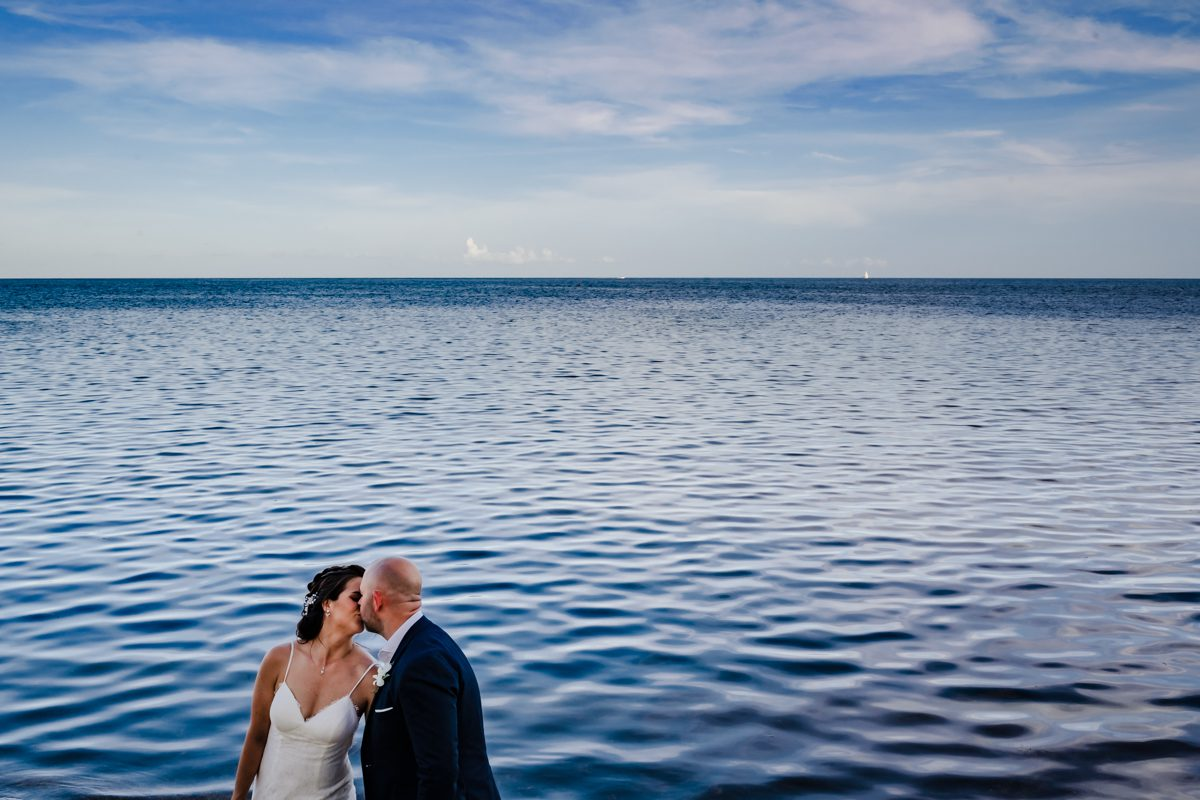 Bride and Groom kiss next to Atlantic Ocean in Key West, Florida.