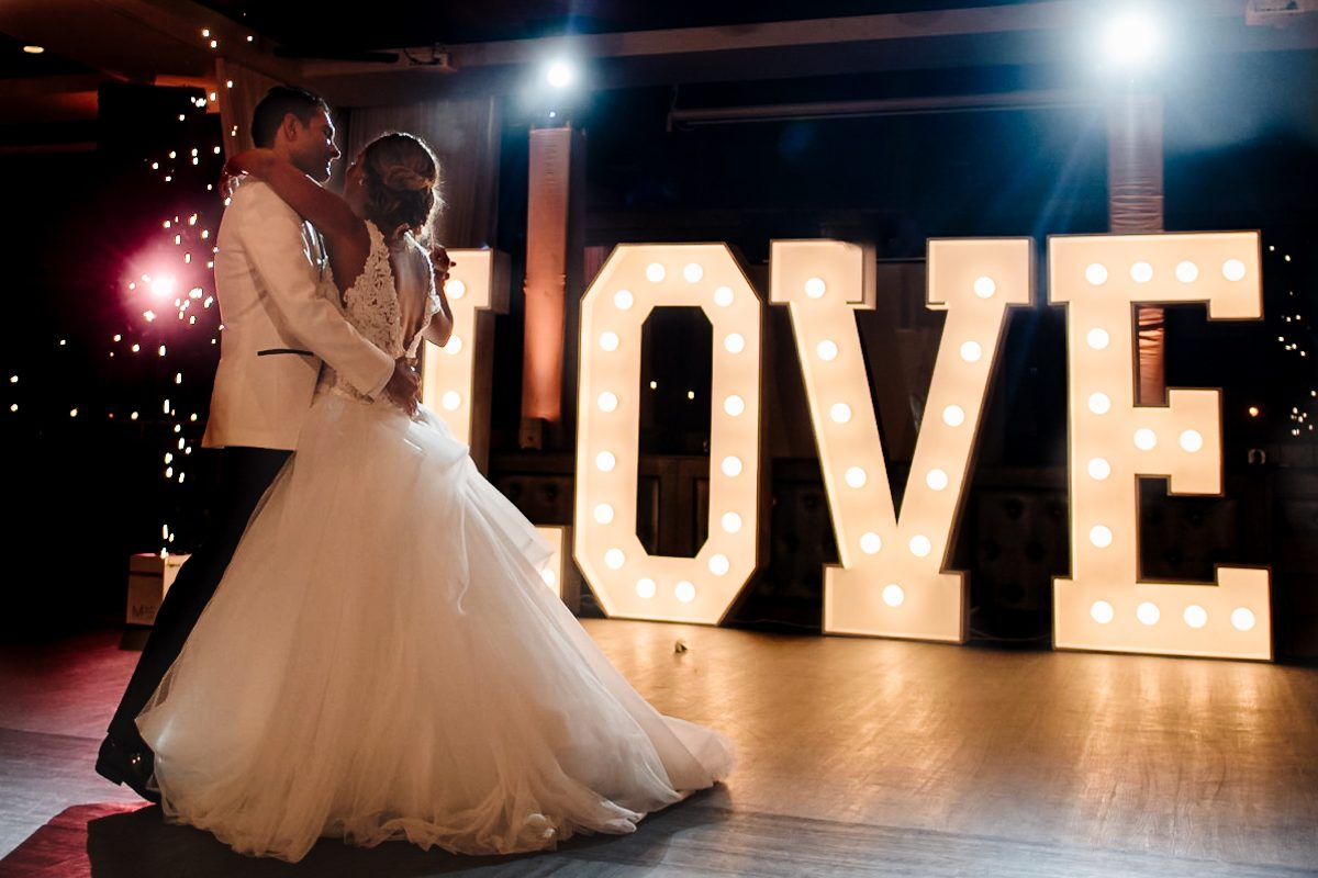Newly Wedded Couple Dance In Front Of Love Sign