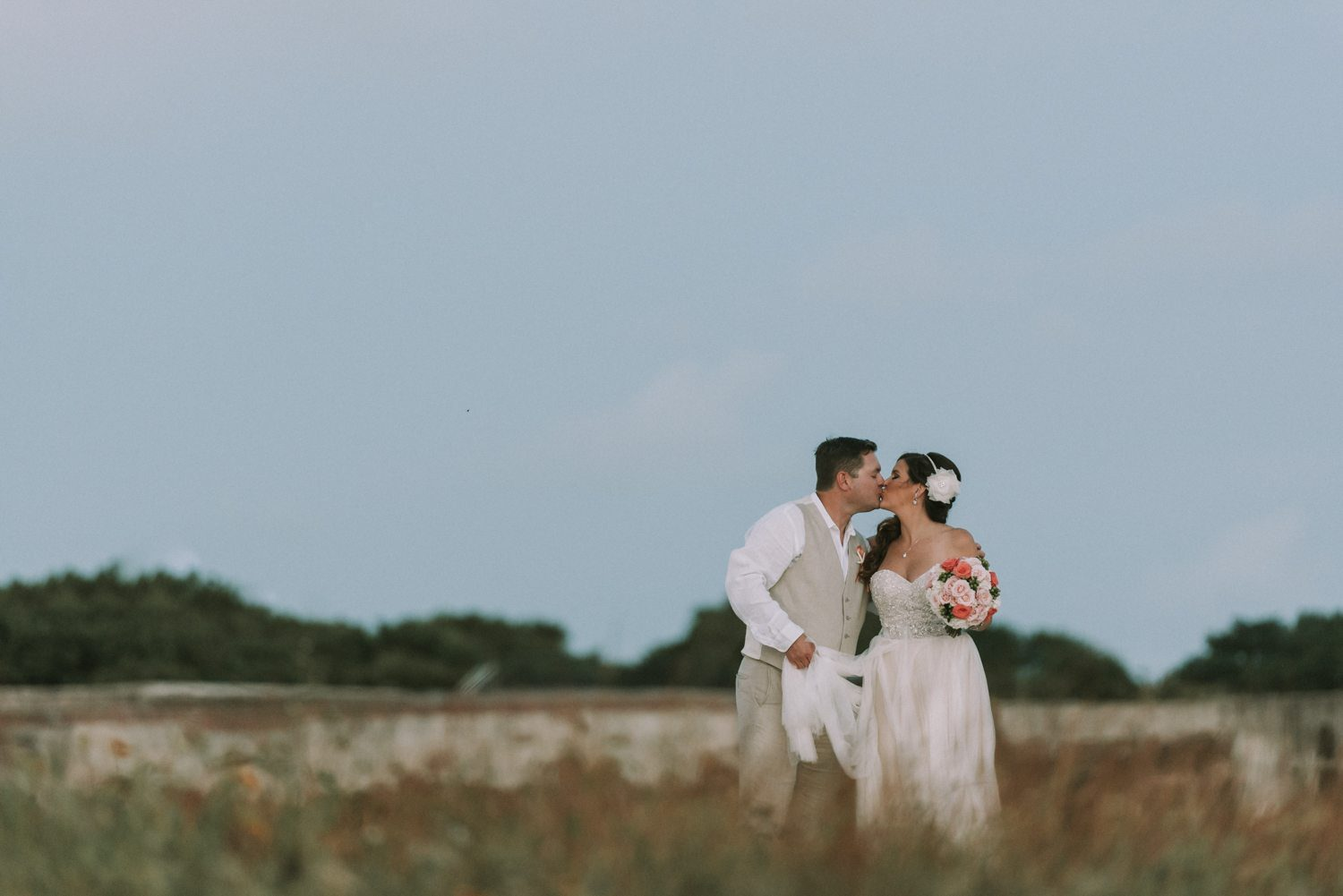 bride and groom kissing on the beach at fort zachary taylor