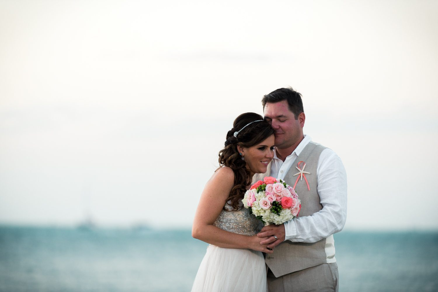 bride and groom laughing while embracing at the beach at fort zachary taylor