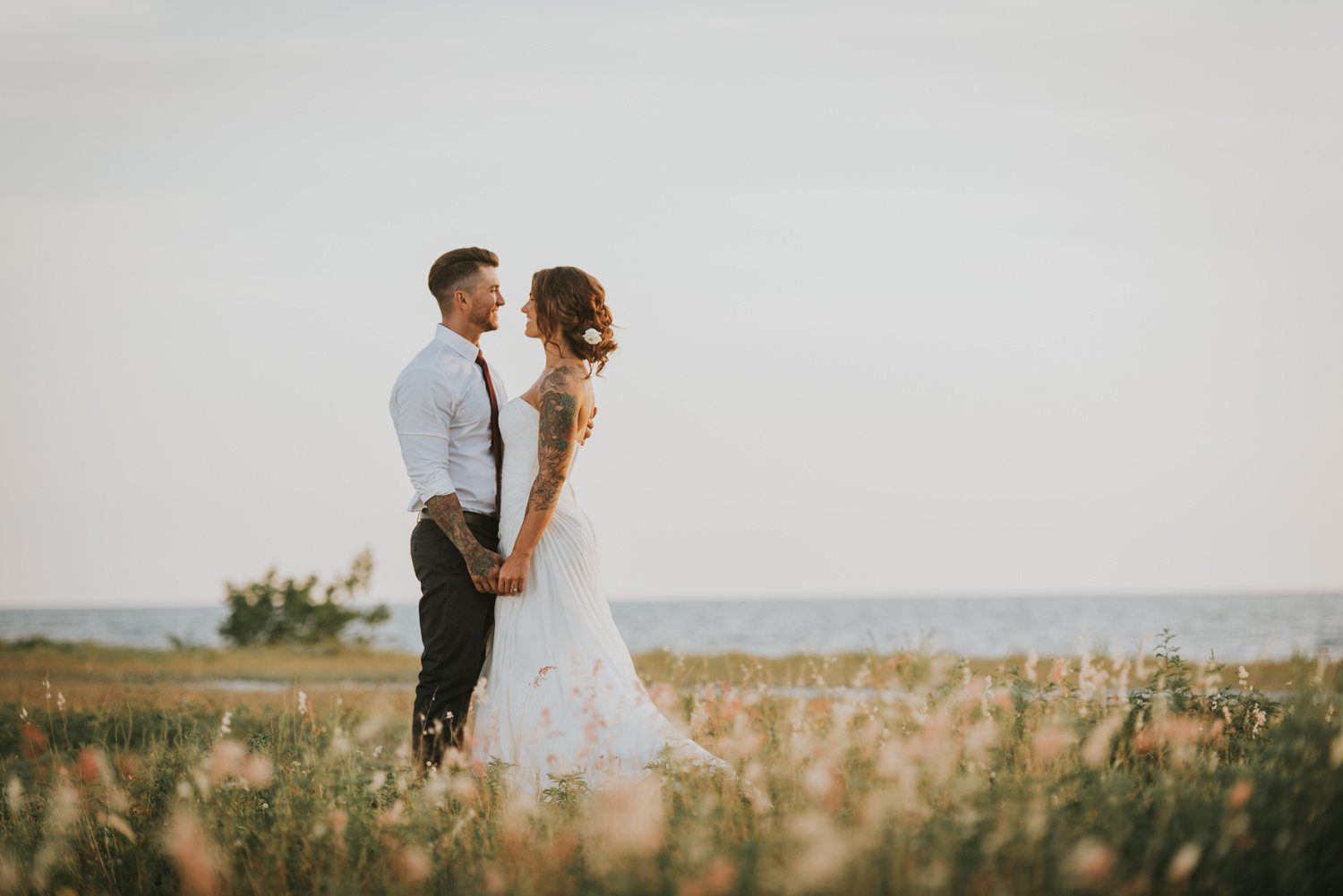 bride and groom holding hands in open field at fort zachary taylor
