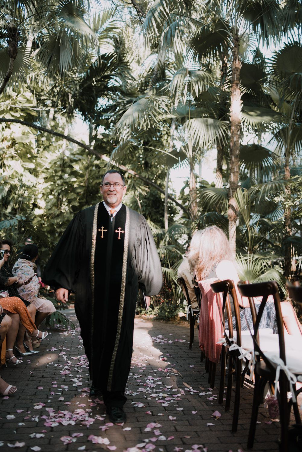 Priest walking down the aisle before a wedding ceremony