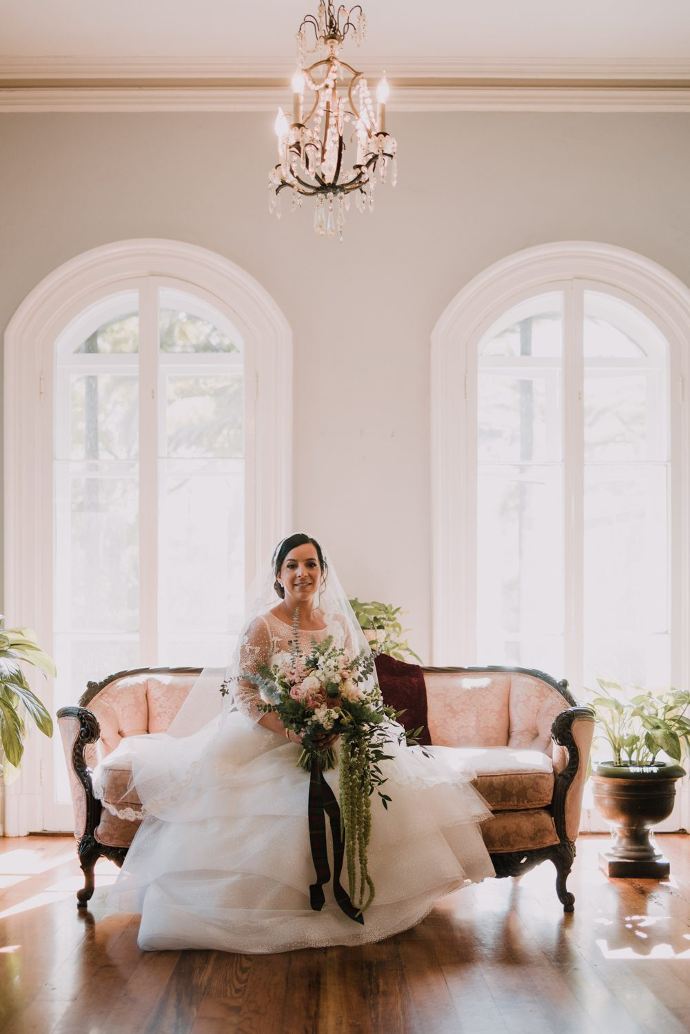Bride sitting on a couch holding her bouquet