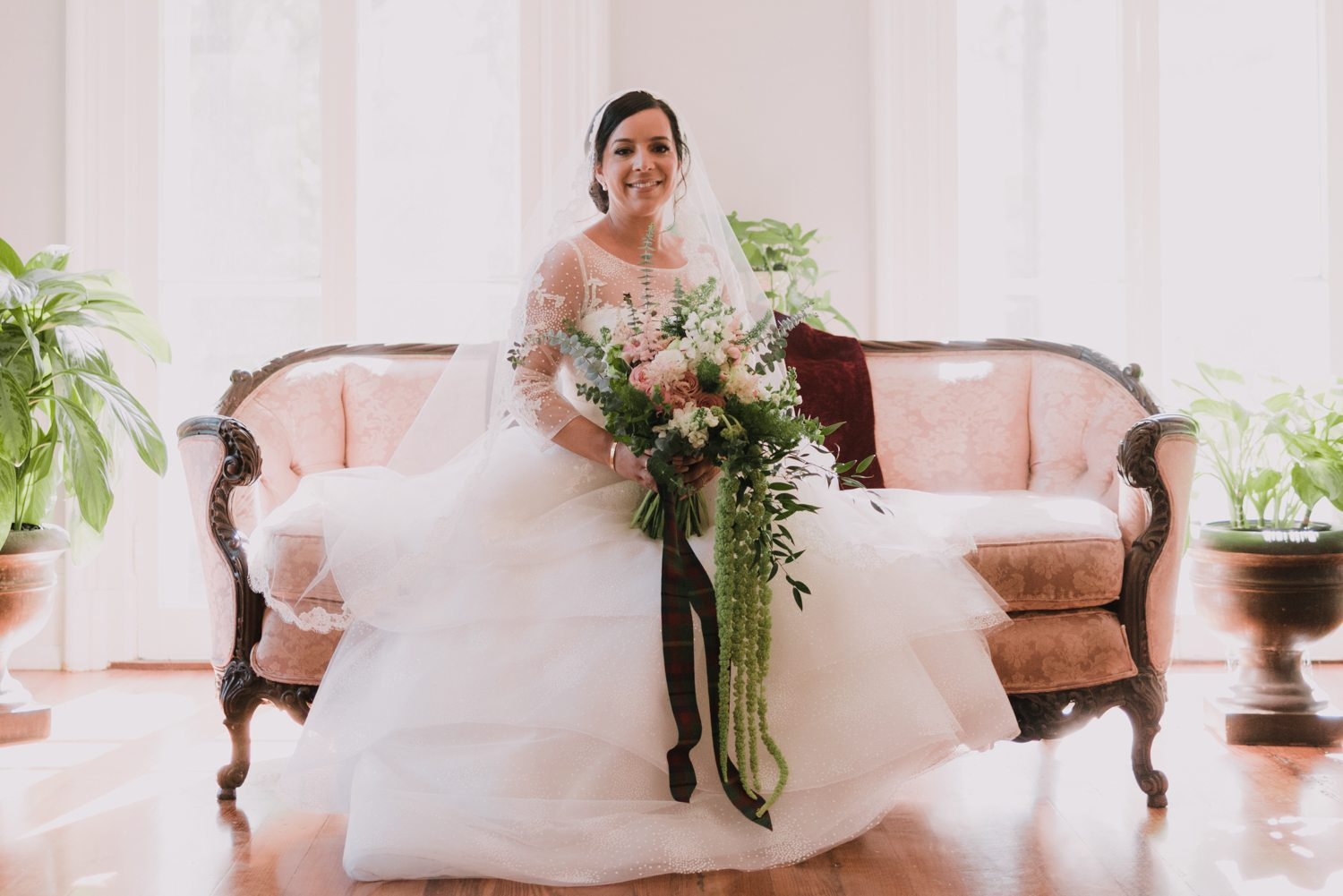 Bride sitting on a couch holding bouquet
