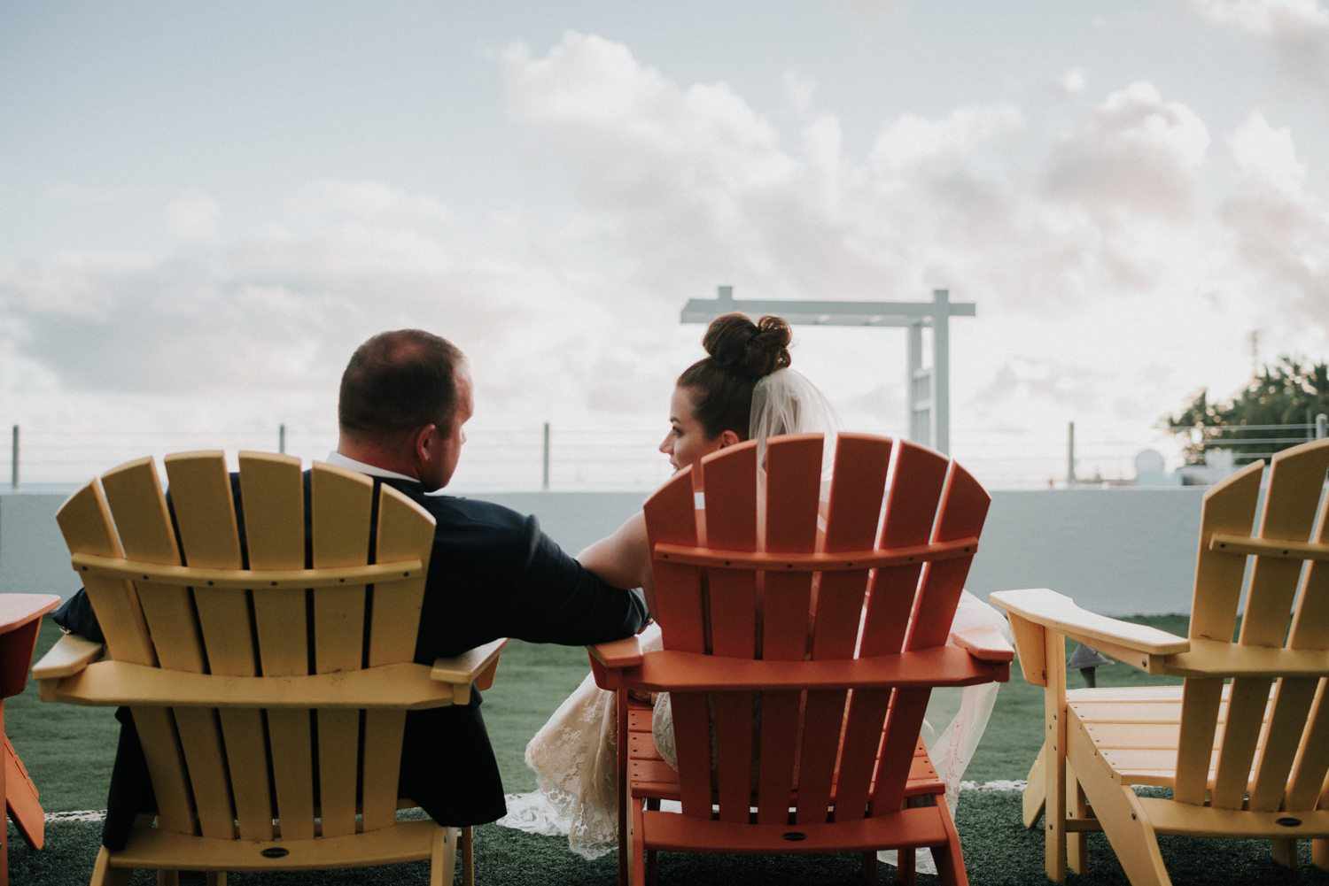 bride and groom sitting in large chairs smiling at each other