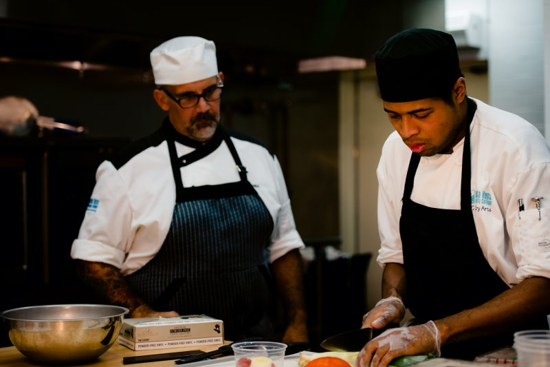 A chef providing instruction to a sous chef