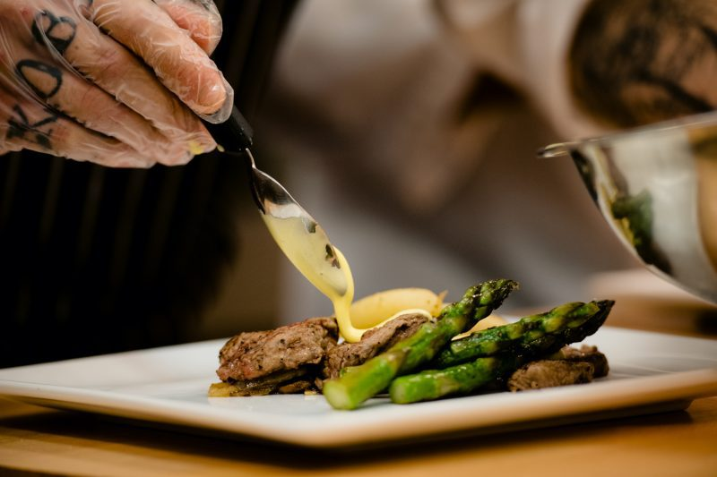 A chef pouring a sauce on asparagus