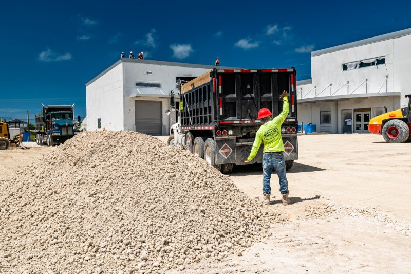 Construction crew moving rock out of a dump truck