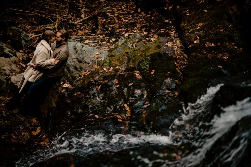 Engagement photoshoot of couple next to a river in Asheville