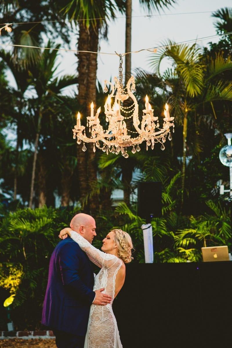 Bride and groom dancing under a chandelier