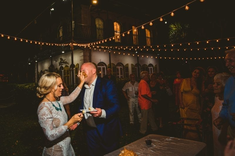 Bride feeding cake to her spouse at a wedding reception