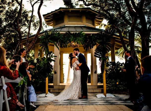 Bride and groom kissing in front of a gazebo in playa largo