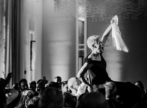 Woman being carried on a chair at a wedding reception