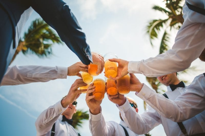 groomsmen clinking glasses at wedding reception at southernmost beach resort