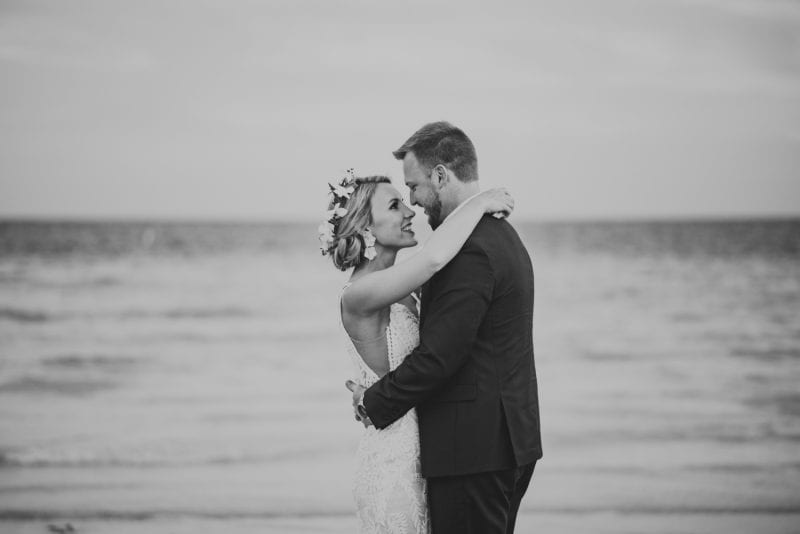 bride and groom smiling at each other for portrait on the beach at southernmost beach resort