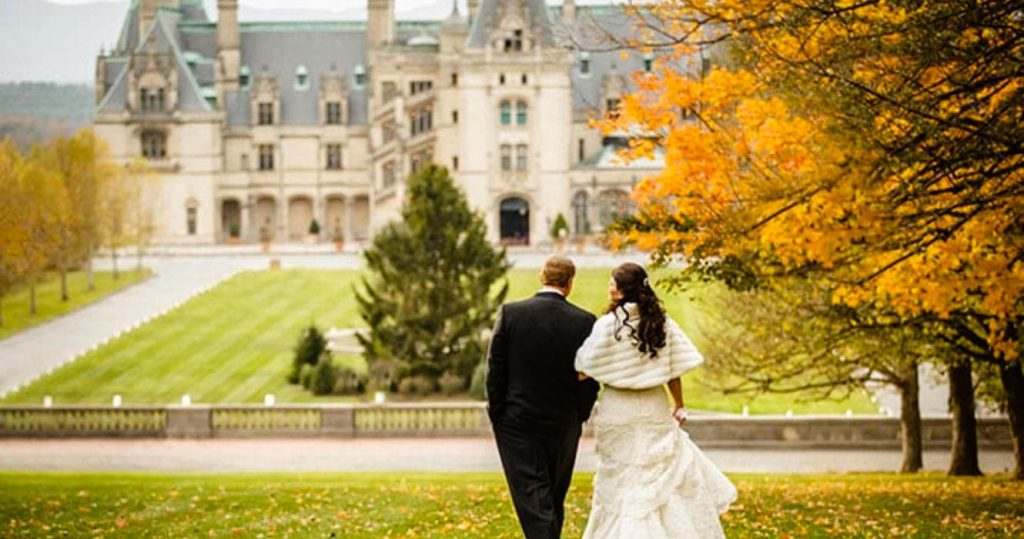 Couple walking amongst the trees in fall for their wedding at the Biltmore.