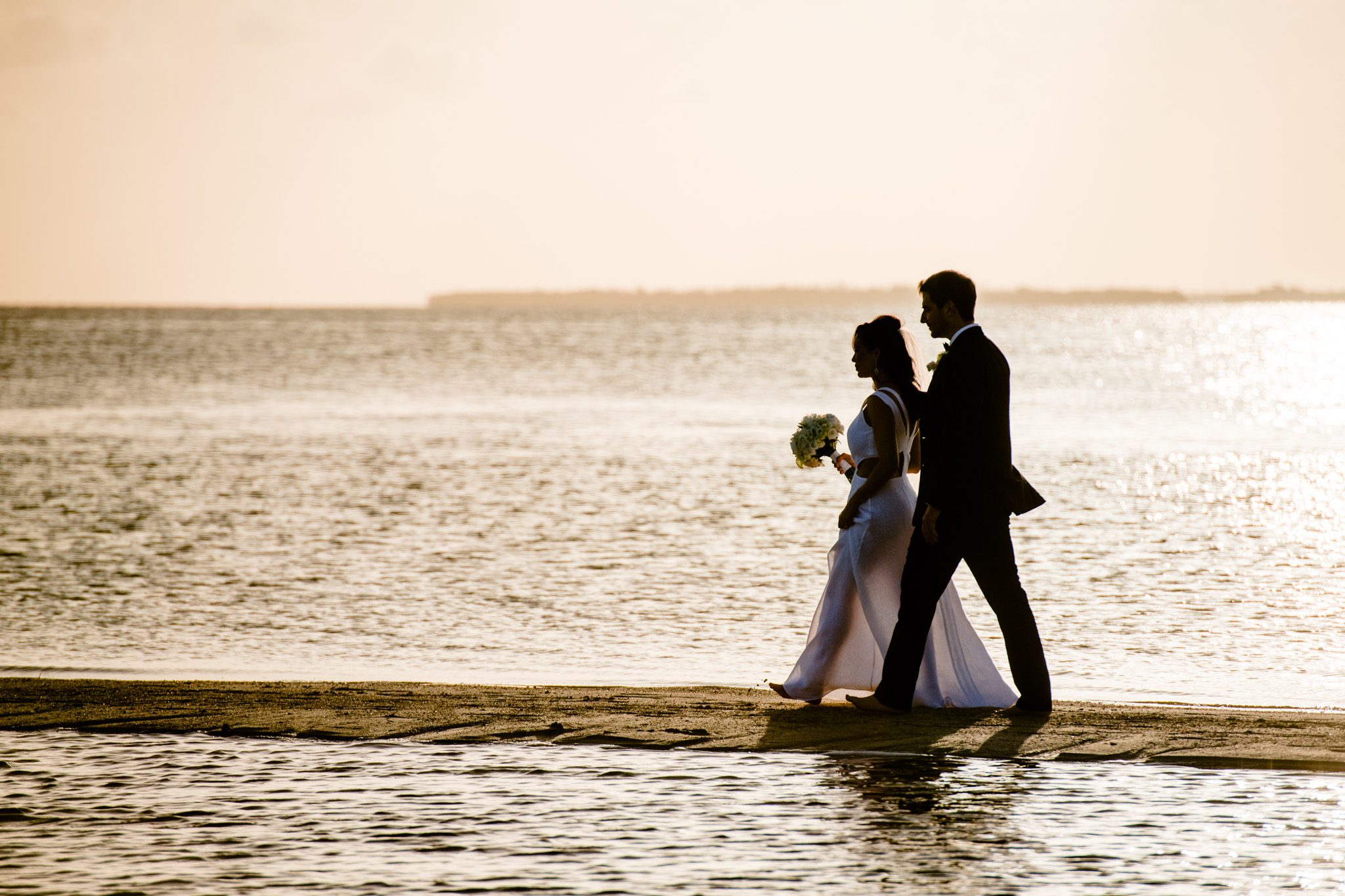 newlyweds walking on the beach at sunset