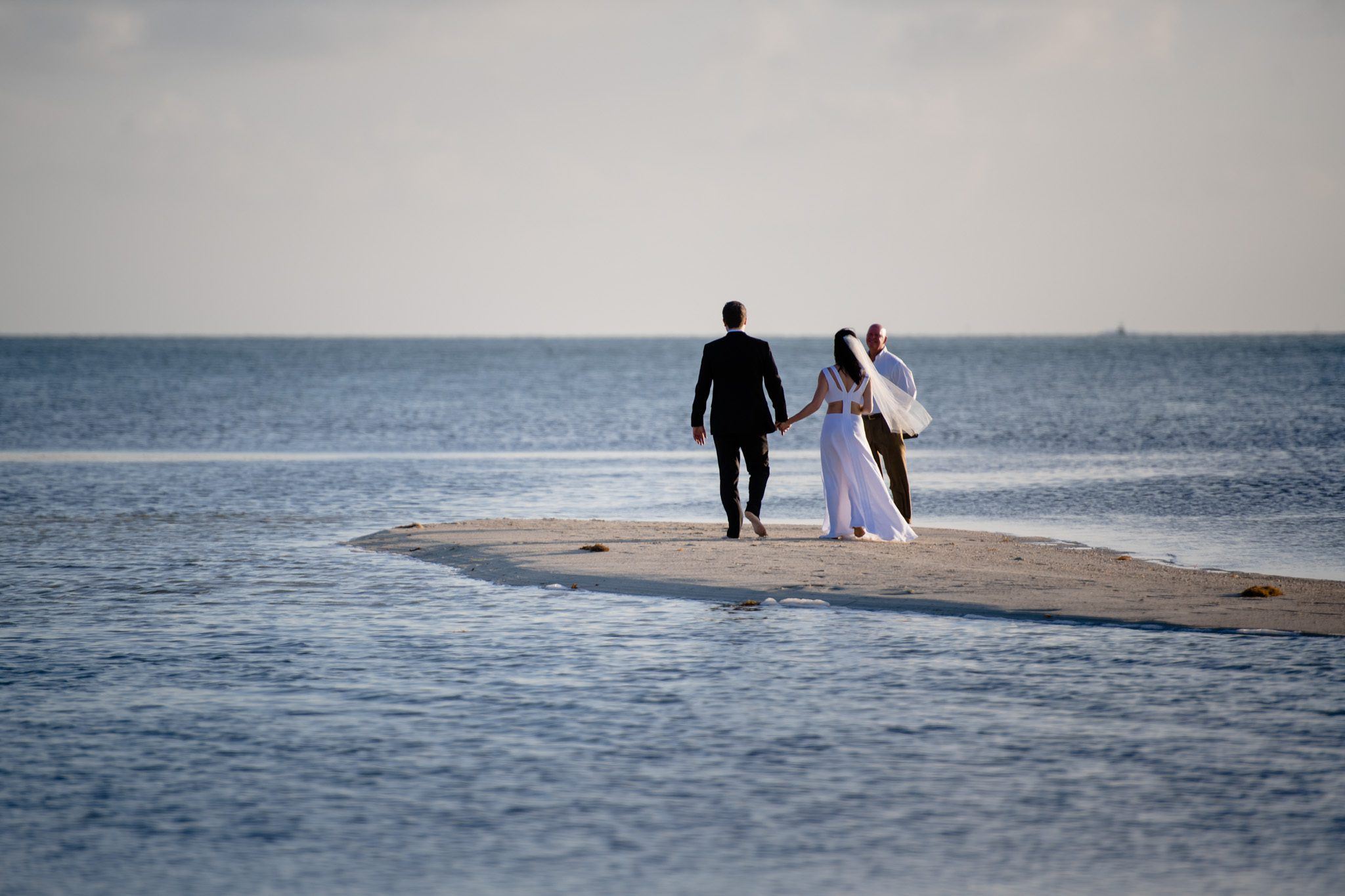newlyweds holding hands at the beach on little palm island
