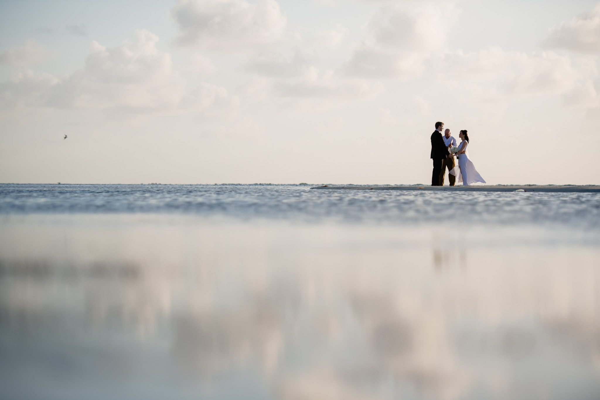 couple standing on the beach after getting married