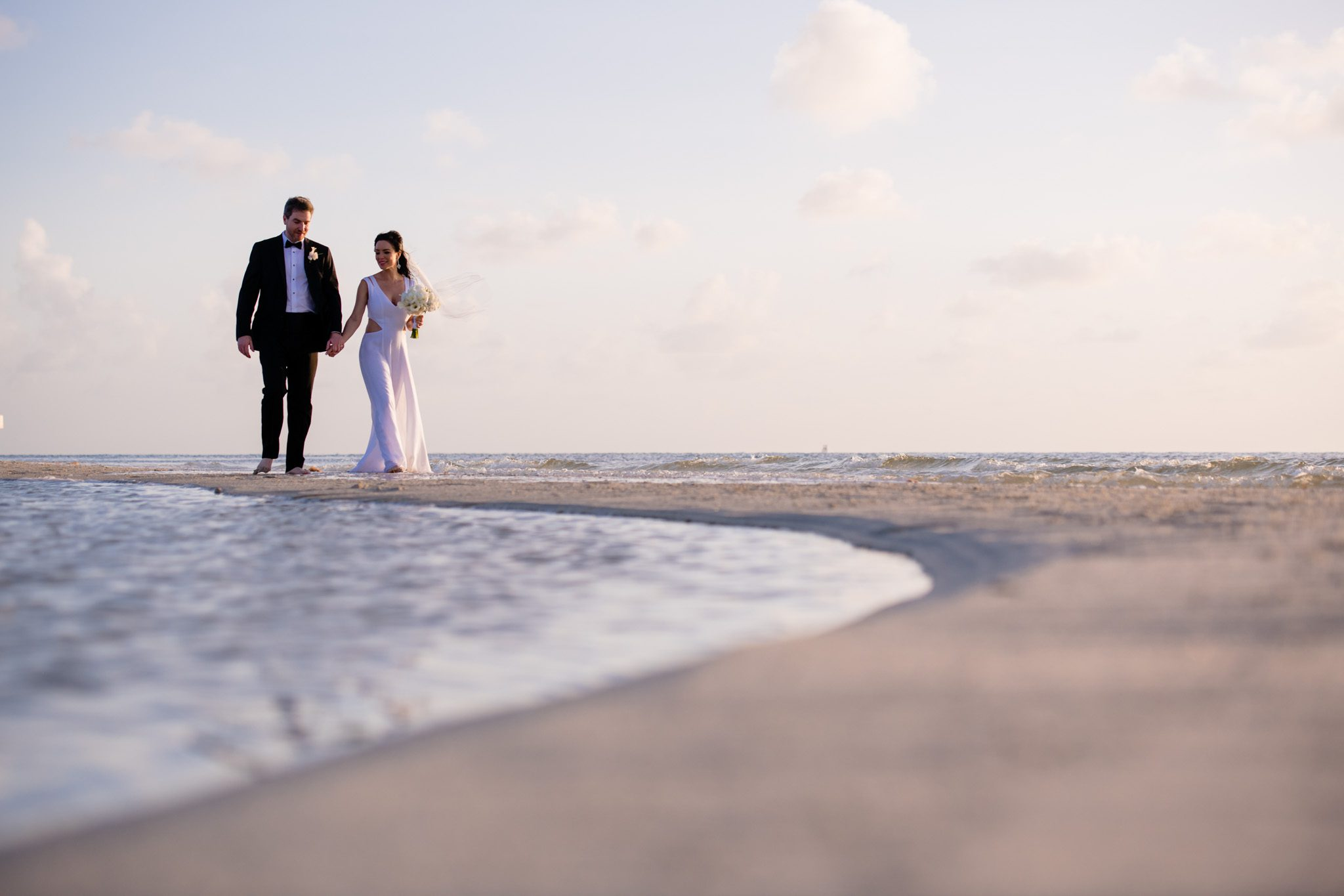newlywed couple walking next to the ocean in key west