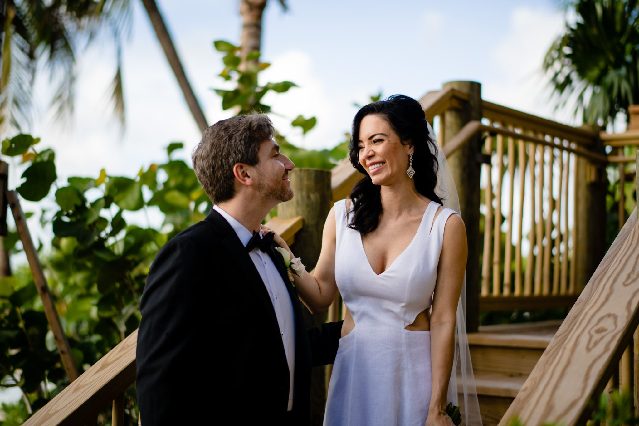 bride and groom smiling at each other, standing on the beach