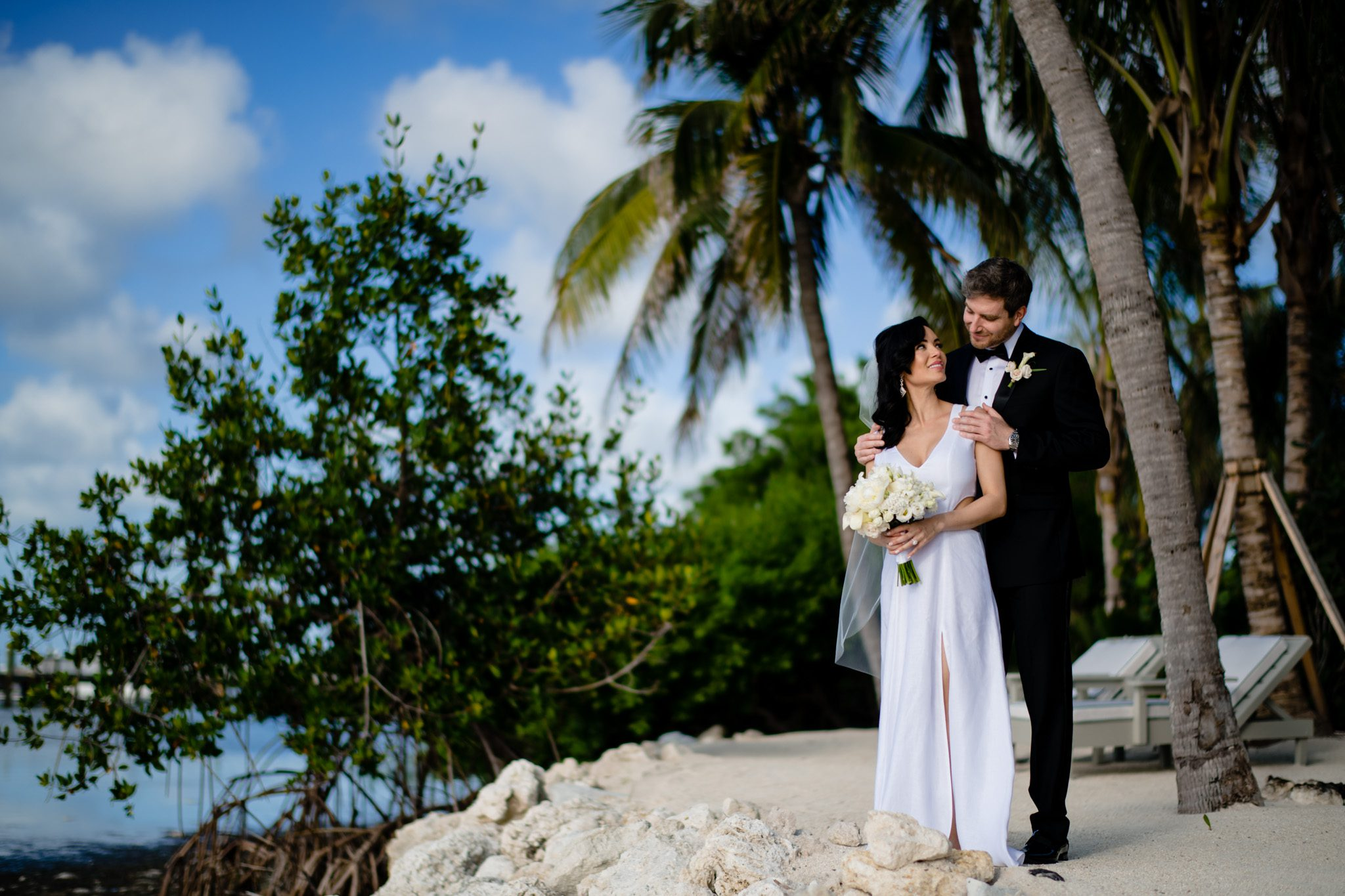 bride and groom standing on the beach at little palm island, looking at each other