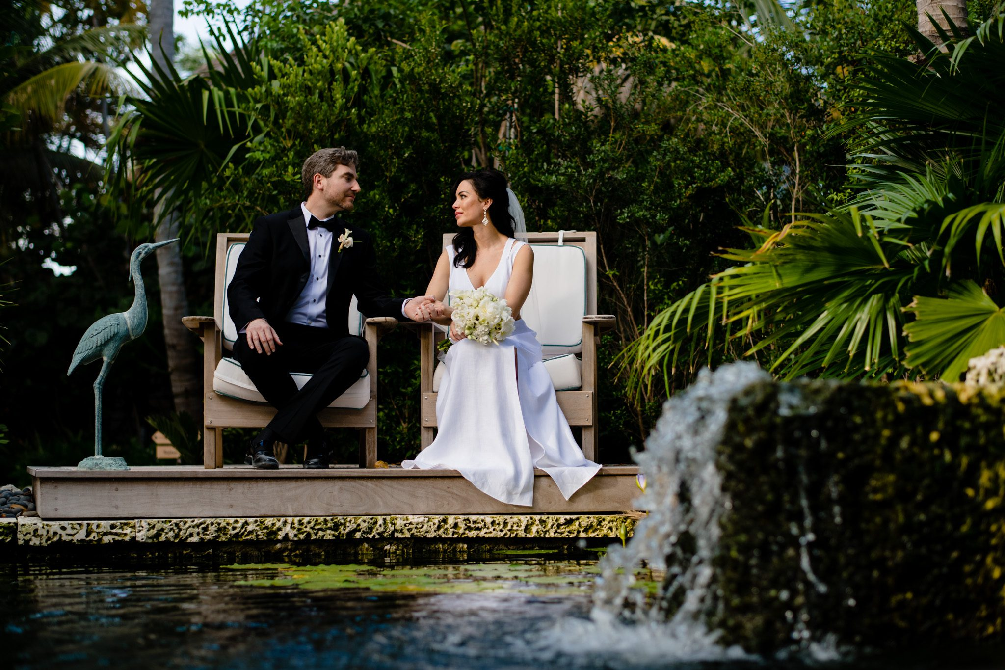 bride and groom sitting in chairs near a water feature on palm island