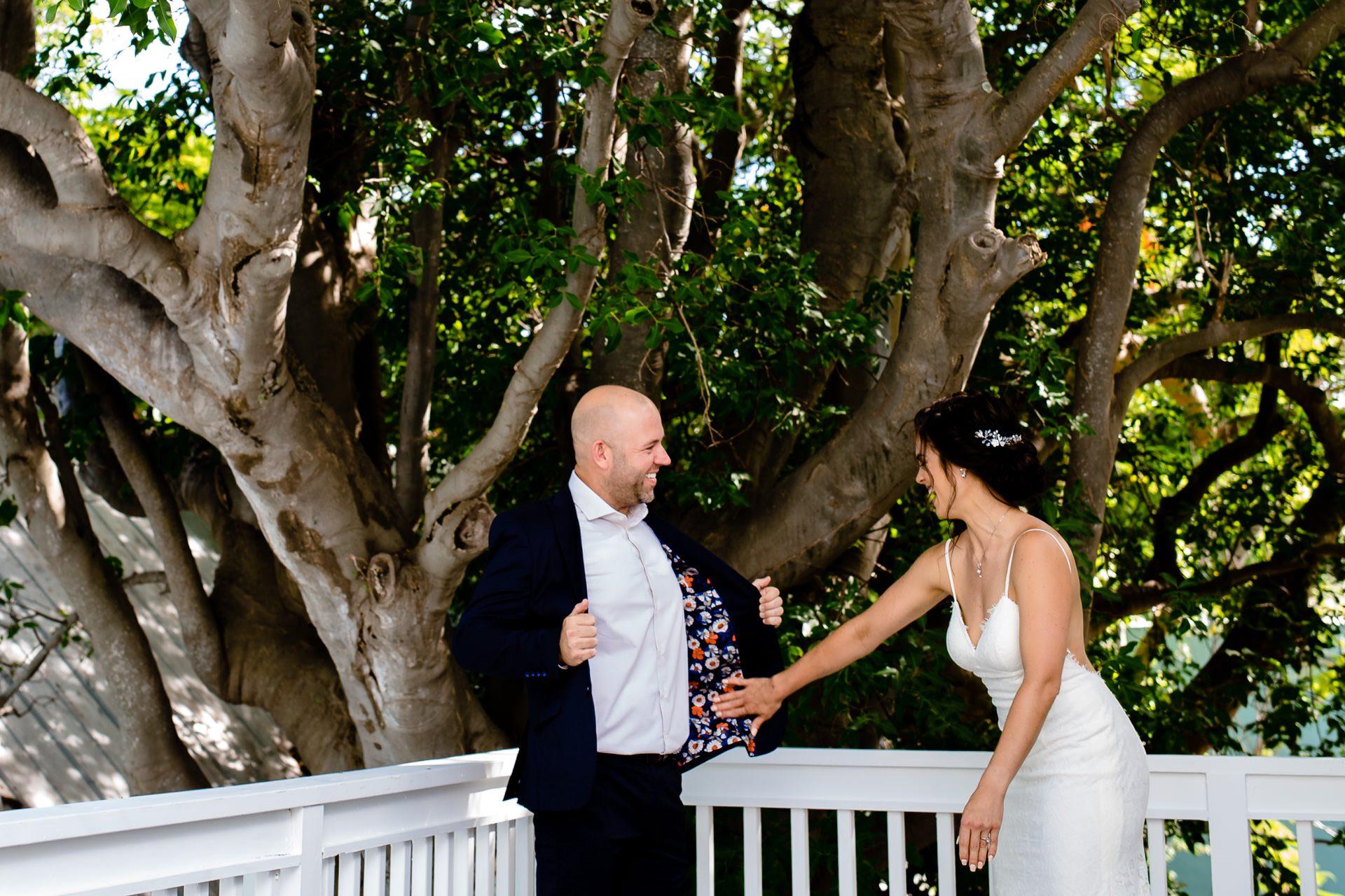 Bride touching her groom's suit jacket.