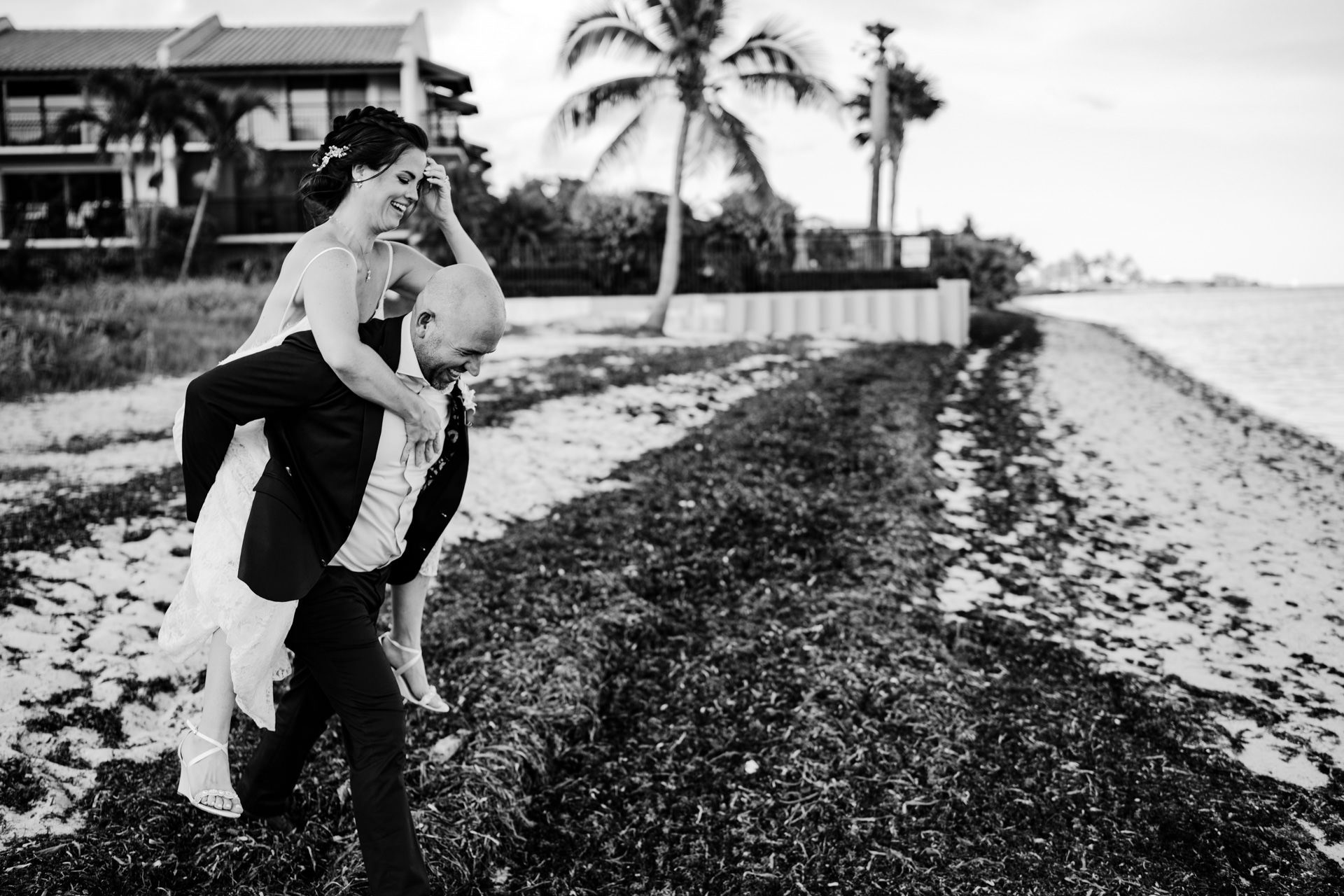 Groom carrying his bride on his back at the beach in key west after eloping.