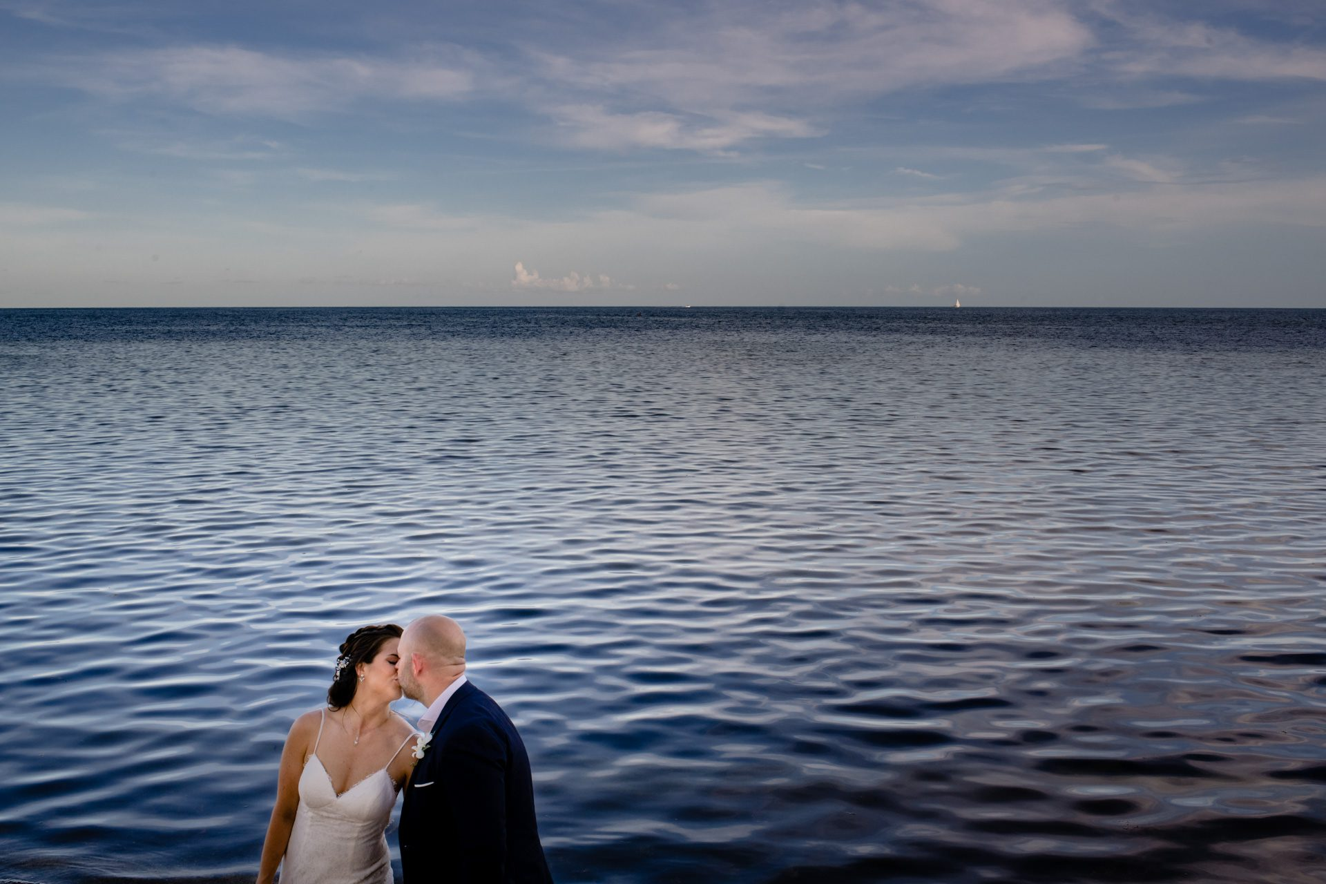 Bride and groom kissing with the ocean in the background in key west.