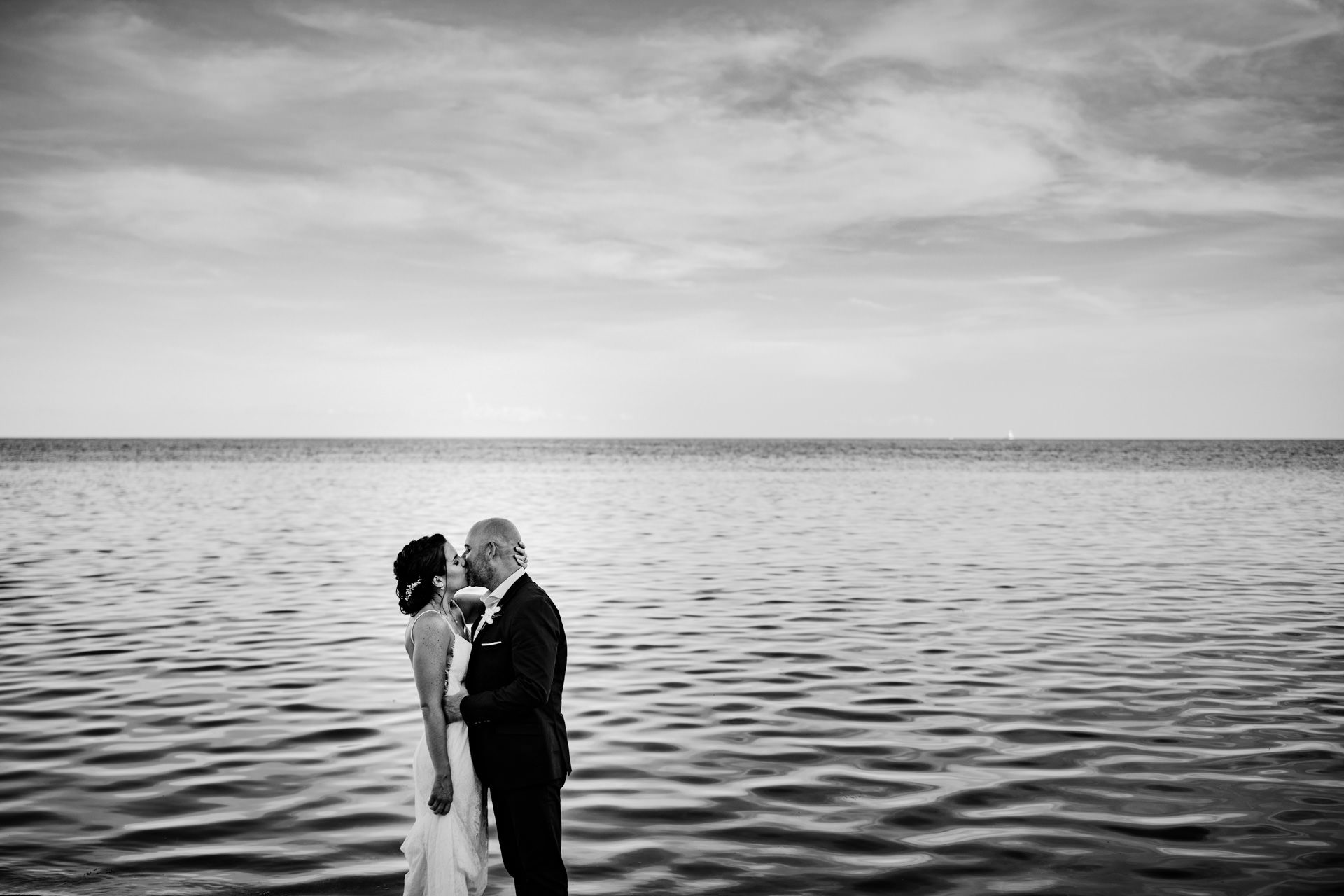 Bride and groom kissing with the ocean in the background at key west.