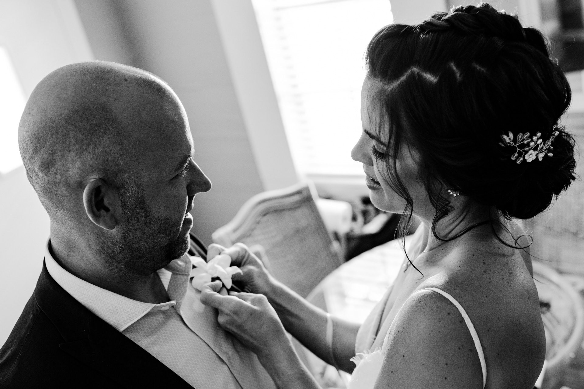 Bride adjusting her grooms lapels before getting married at old town manor.