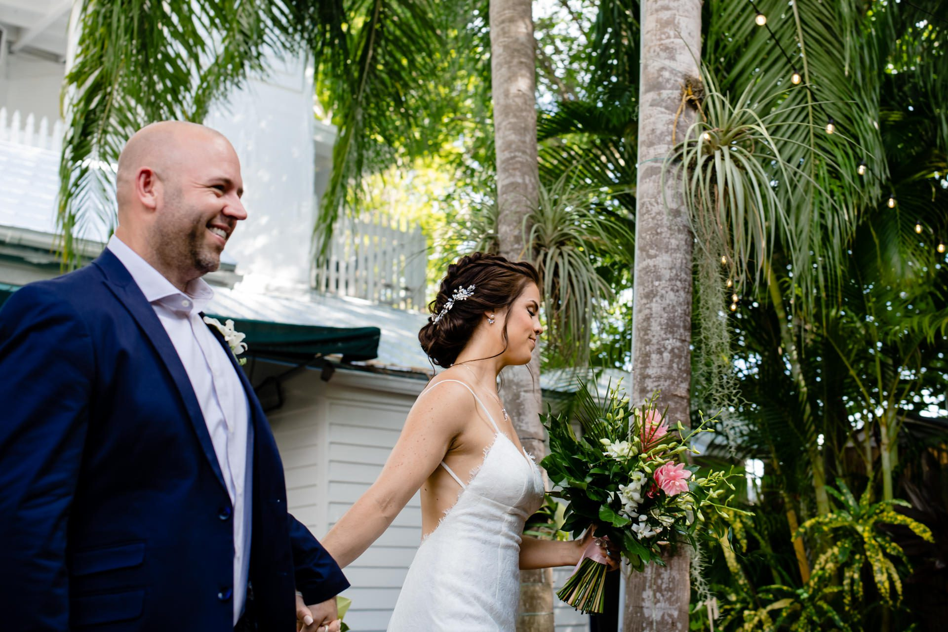 Bride holding flowers and walking with her groom to be eloped in Key West.