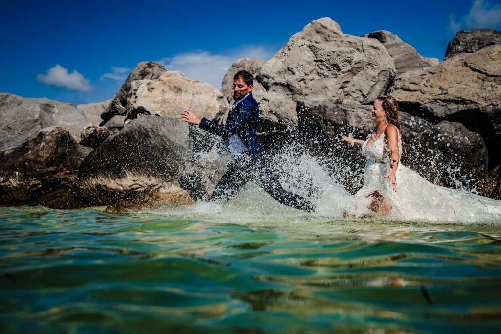 bride chasing groom during trash the dress session