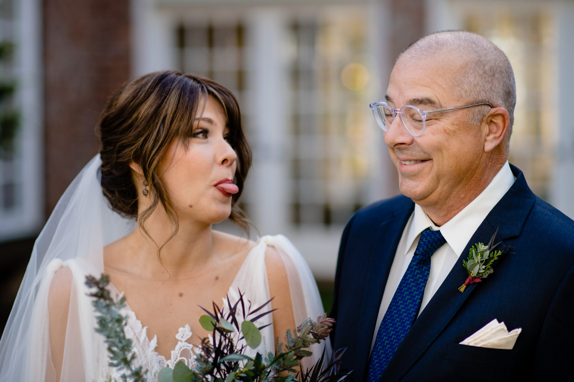 Bride sticking her tongue out at her father before walking down the aisle