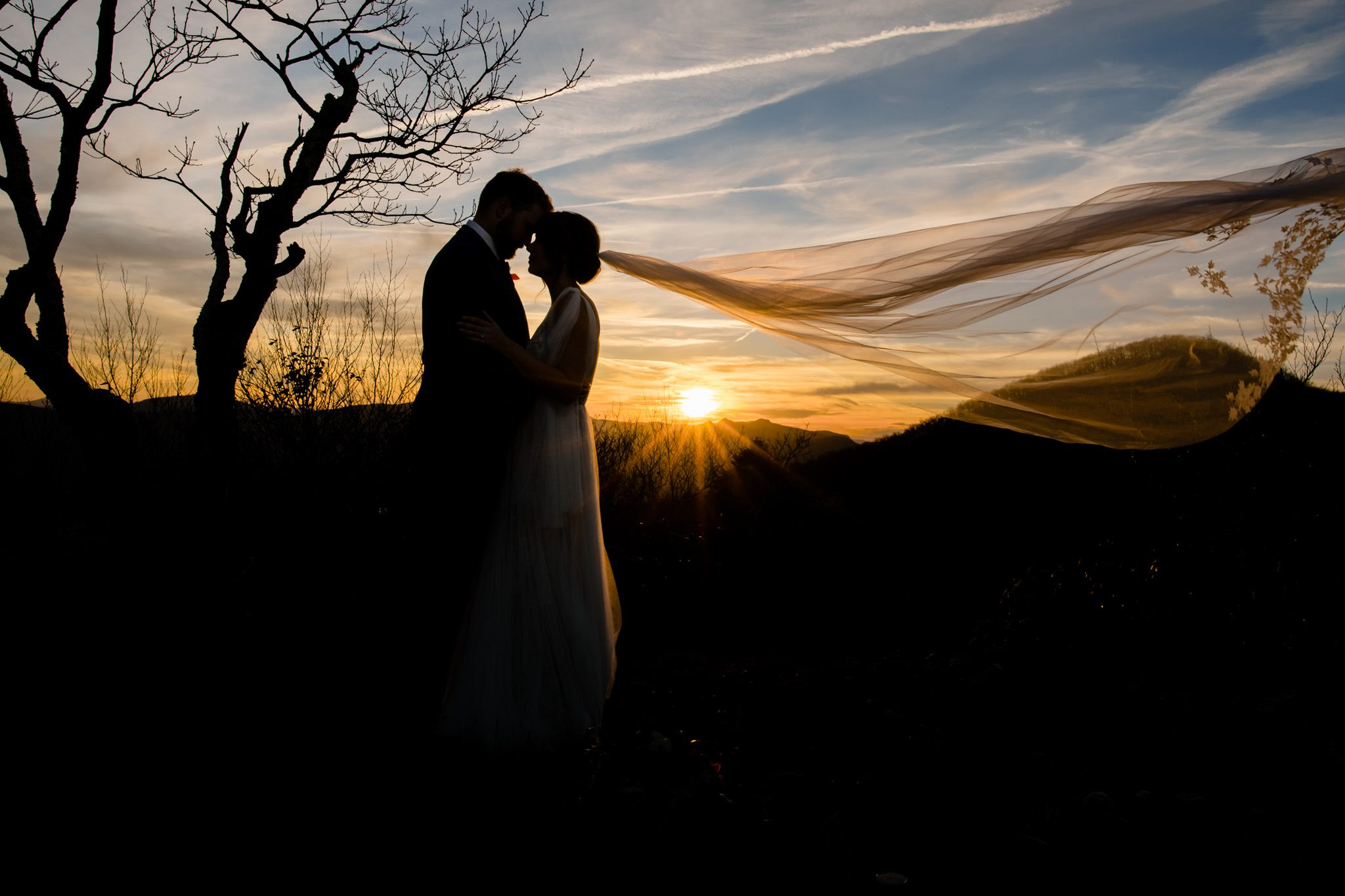 Bride with her veil flowing in the wind at sunset in the Asheville mountains