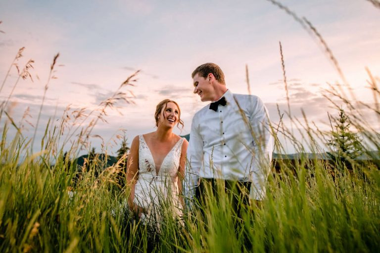 newly eloped couple smiling as they walk through high grass